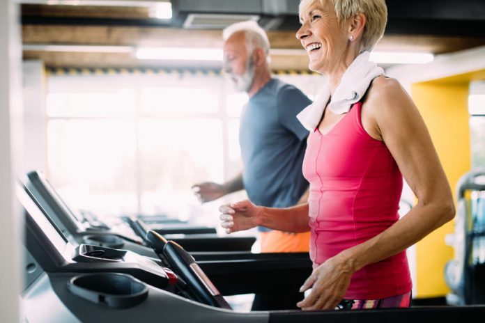 Senior man and woman exercising on treadmills